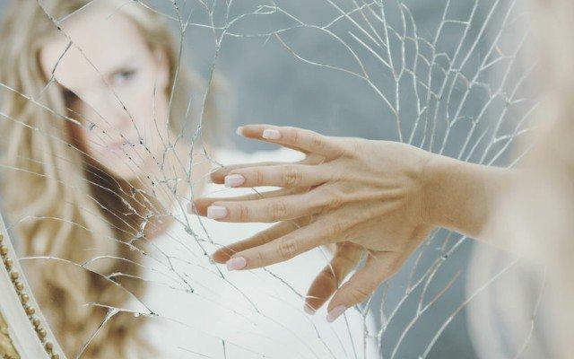 Mulher se olhando em espelho quebrado.
