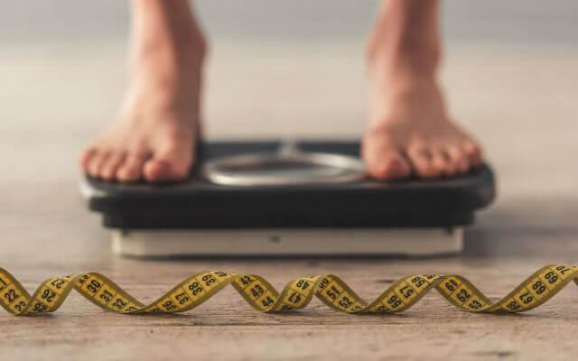 Uma pessoa em pé na balança, com uma fita métrica jogada ao chão.