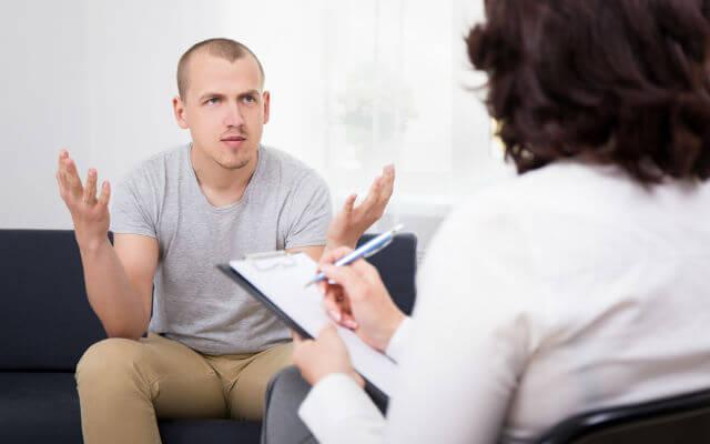 homem sentado no sofá em frente a uma médica ou terapeuta