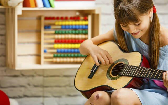 menina segurando um violão