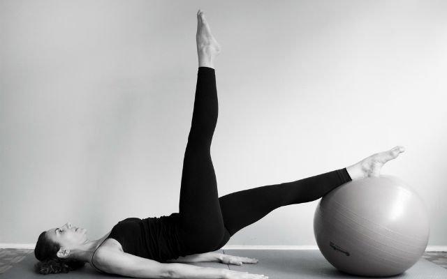 mulher alongando-se na bola de pilates