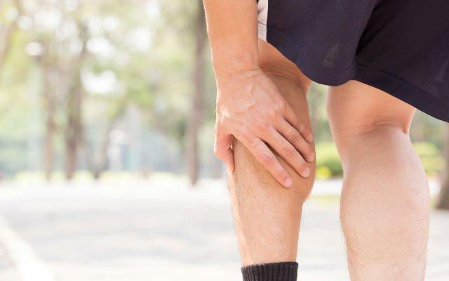 homem segurando a perna