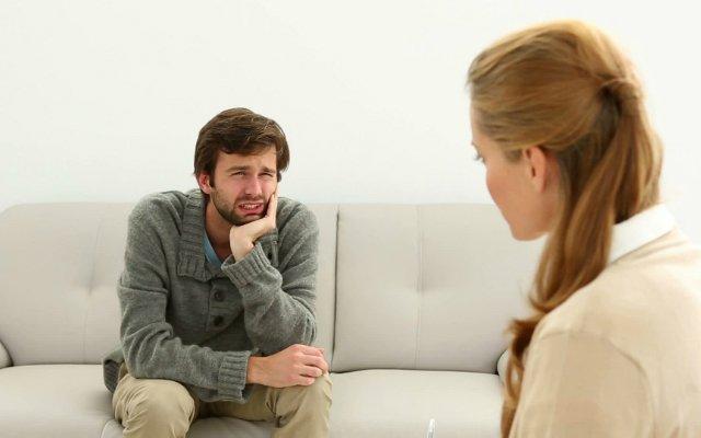Homem triste, sentado no sofá em frente a uma psicóloga.
