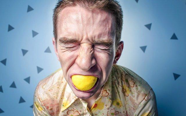 Homem com um limão da boca