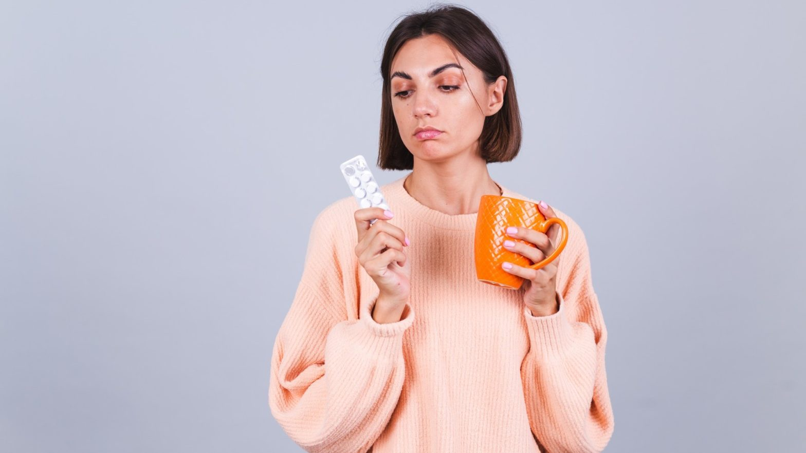 Mulher segurando cartela de comprimidos para labirintite.