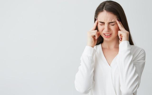 Mulher com os dedos indicadores na cabeça sinalizando dor.