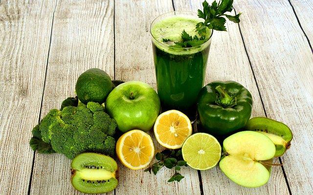 Um copo com um suco verde, com os ingredientes ao lado. Sendo maçã, laranja, limão, brócolis, pimentão e kiwi.