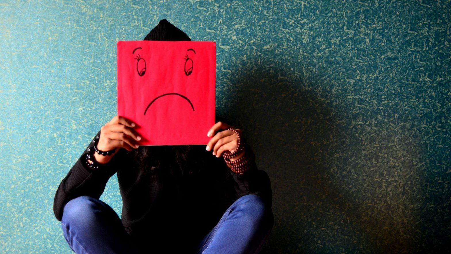 Homem sentado segurando um cartaz vermelho com desenho de expressão triste.