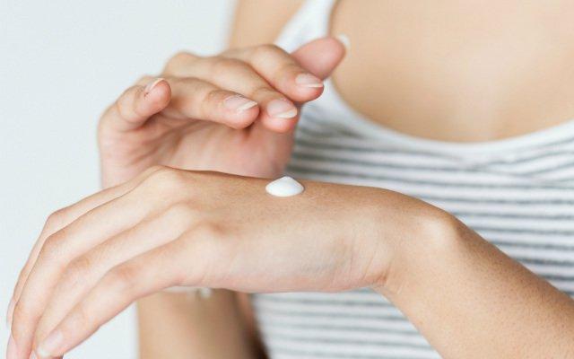 Mulher passando um pouco de pomada para impingem na parte superior da mão.