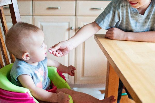 Mae alimentando o seu filho apos desmame.