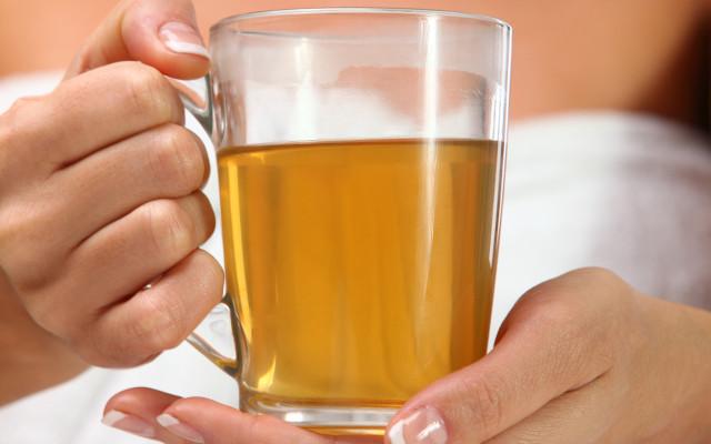Mulher segurando xícara de chá de erva-de-são-joão.