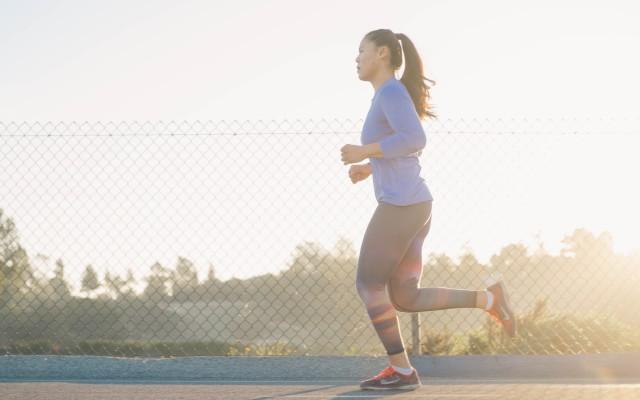 Mulher correndo durante o nascer do sol.