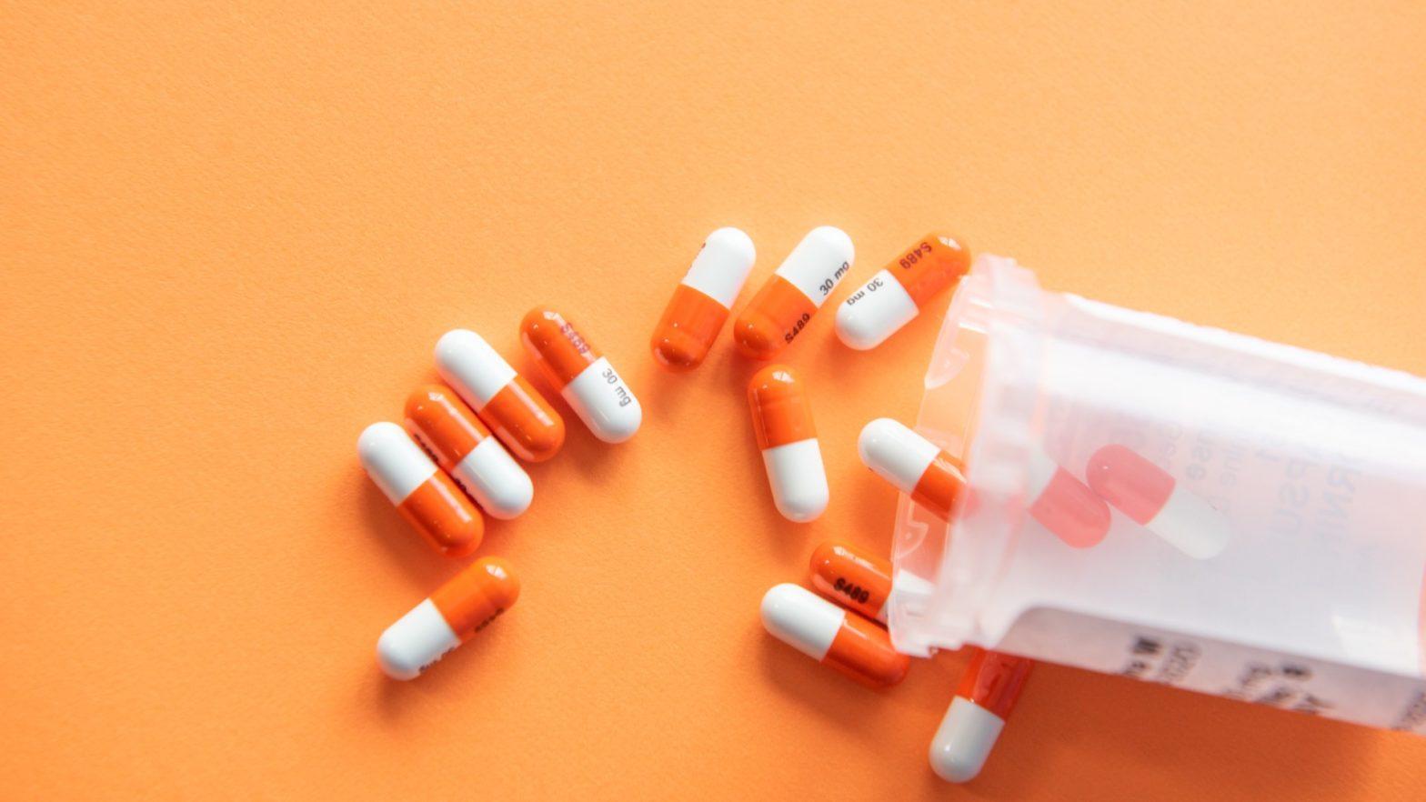 comprimidos espalhados por cima da mesa laranjada