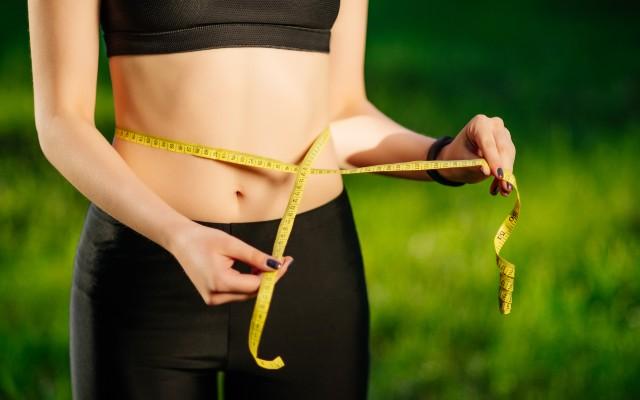 Imagem de uma mulher medindo a cintura com uma fita métrica