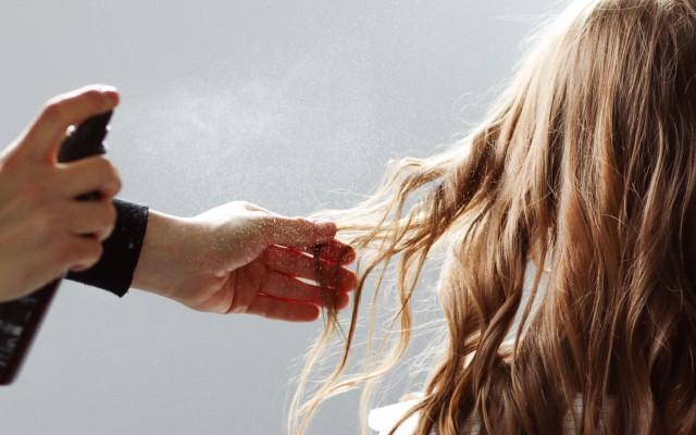 Cabeleireiro borrifando Bepantol liquido nos cabelos de uma mulher.