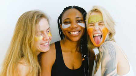 3 mulheres sorrindo e com o rosto cheio de base colorida.