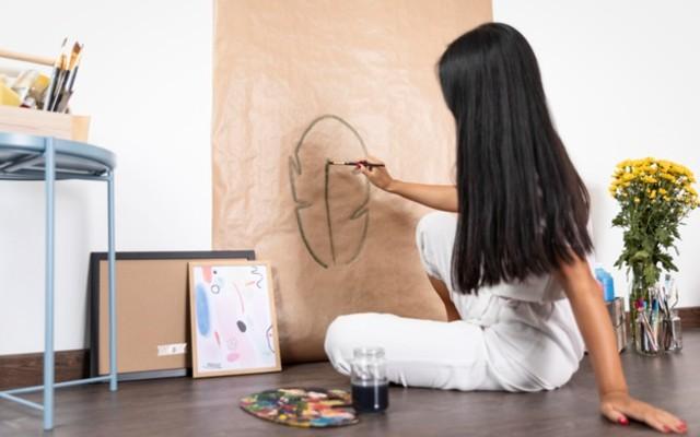 mulher senatada no chão pintando em uma folha