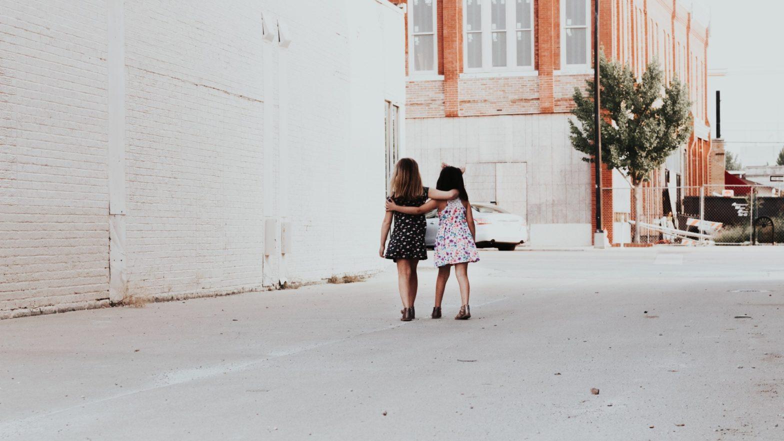 Imagem de duas crianças caminhando juntas, abraçando-se com afeto.