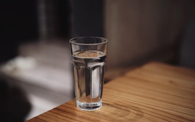Um copo de água em cima da mesa.