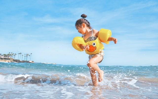 Uma criança com boias nos braços, brincando na beira do mar.
