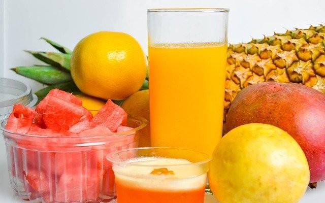 Alimentos ricos em vitamina C como laranja, abacaxi, manga sobre a mesa.