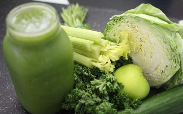 Suco verde feitos com alimentos como repolho, salsa e pepino sobre a mesa.