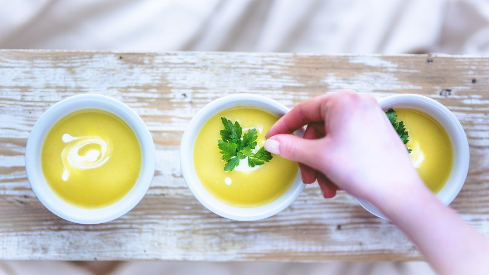 3 pratos de sopas amarelas uma ao lado da outra e uma mão feminina colocando uma folha de salsinha na sopa do meio.