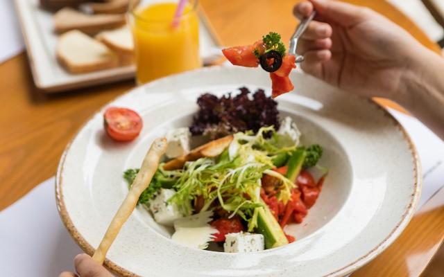 Um prato de salada com alface e tomate, ao lado um copo de suco de laranja.