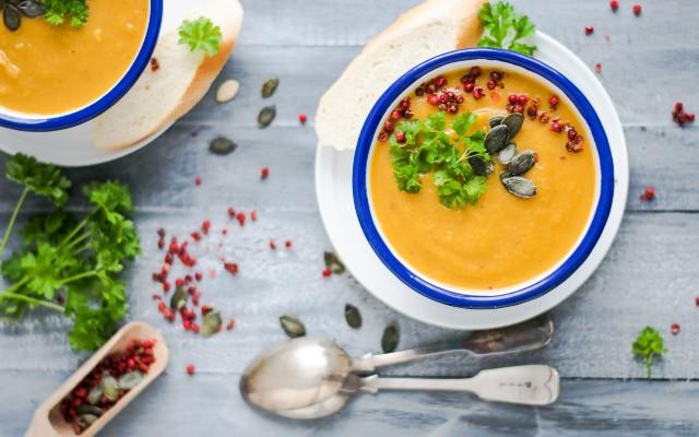 Dois bowls de sopa, com uma colher ao lado.