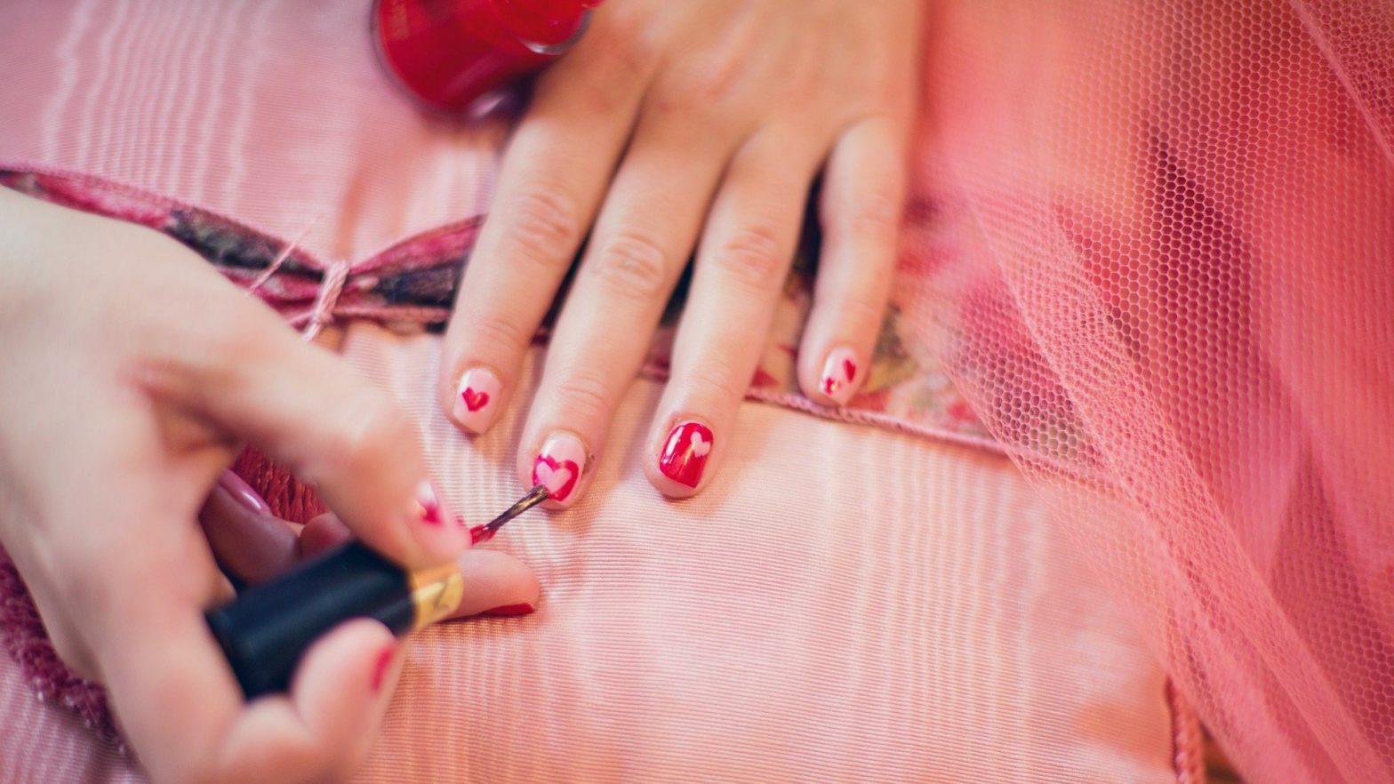 Unhas sendo decoradas com corações feitos com um esmalte vermelho.