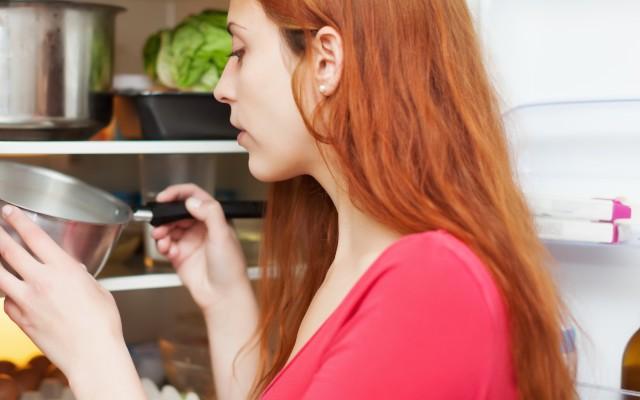 Mulher olhando uma panela dentro da geladeira