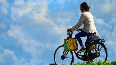 Mulher andando de bicicleta ao ar livre.