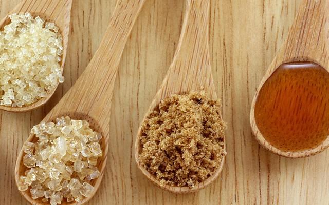 Um colher de pau do lado da outra recspetivament com mel, açucar de coco, demerara e cristal sob uma mesa.