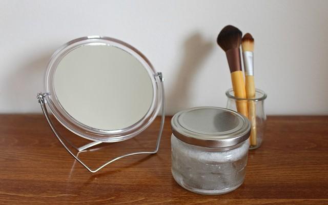 Um espelho de mesa redondo, um pequeno pote de vidro e um porta pincéis de maquiagem contendo dois pincéis. Diminuir os itens de beleza é uma dica do skinimalism.