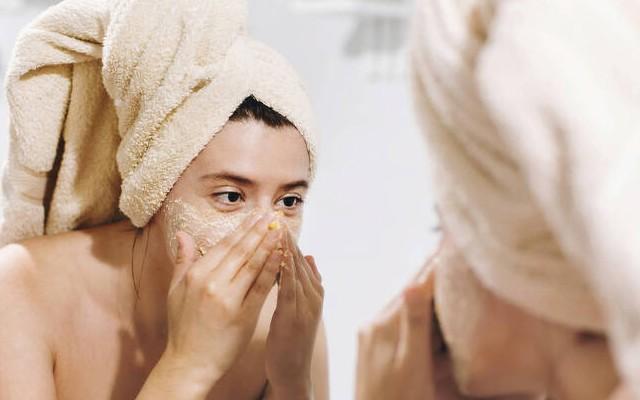 Mulher com toalha enrolada na cabeça em frente ao espelho passando um cosmético no rosto.
