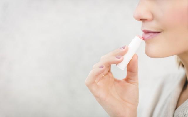 Mulher passando hidratante labial.