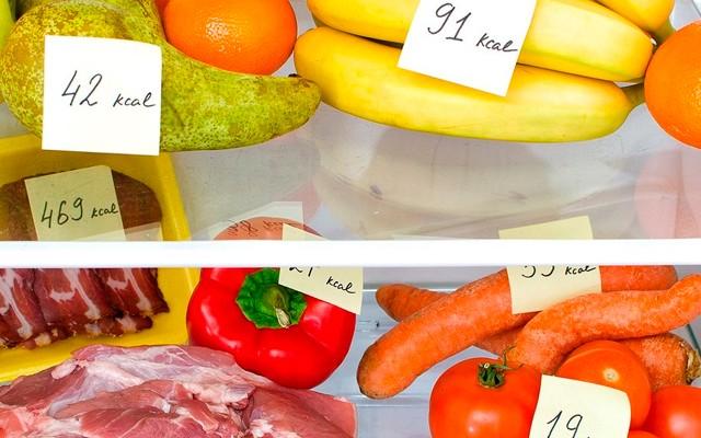Diversas frutas e legumes na geladeira contendo o valor energético (calorias) em cada um.