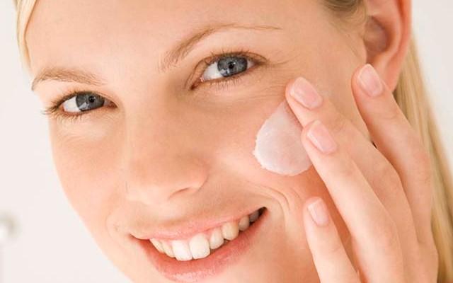 Mulher que segue o skinimalism passando um pouco de creme hidratante no rosto para ter uma pele iluminada e saudável naturalmente.