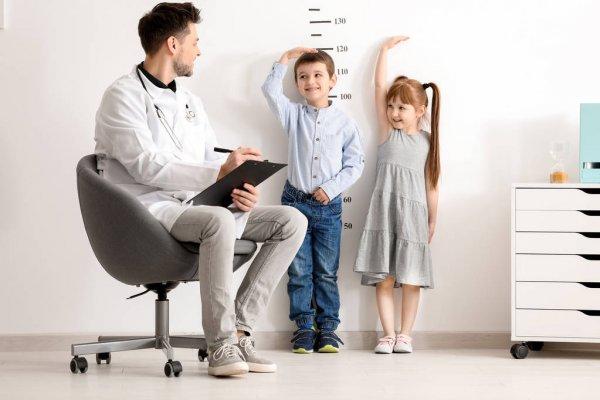 Duas crianças encostadas na parede, medindo suas alturas. Há um homem adulto anotando os valores