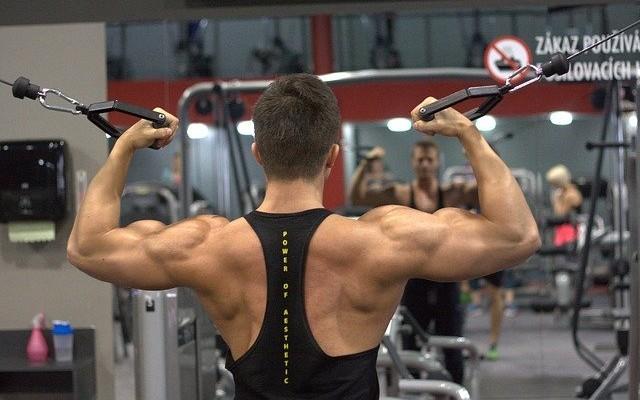 Homem fazendo treinamento de ombros e costas na academia. O hormônio GH ajuda no ganho de massa muscular.