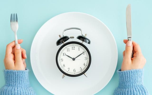 Prato vazio com um relógio em cima, e uma mão feminina de cada lado com garfo e faca.