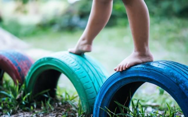 Criança brincado sobre pneus