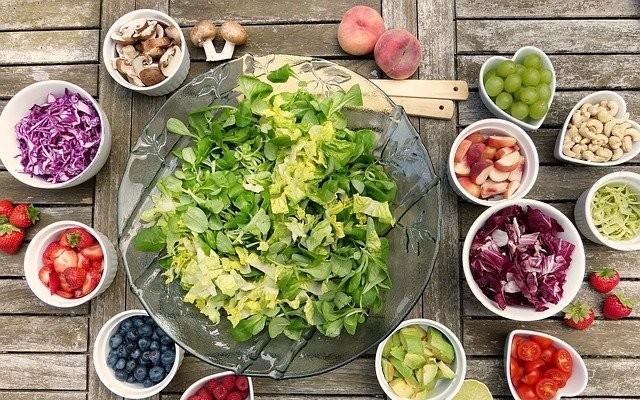 Um prato com salada verde no meio da mesa e ao redor porções de frutas , cogumelos, vegetais e legumes.