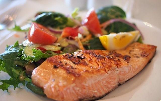 Prato contendo um salmão grelhado e salada.