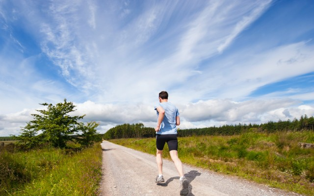 Homem correndo em um local aberto, com grama em ambos os lados.