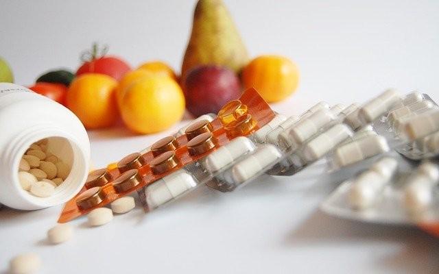Frutas e cartelas de vitaminas para a imunidade baixa.