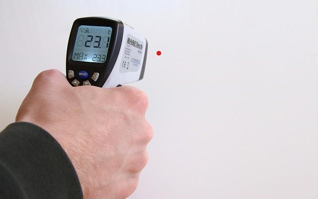 Uma pessoa apontando um termômetro infravermelho para a parede.