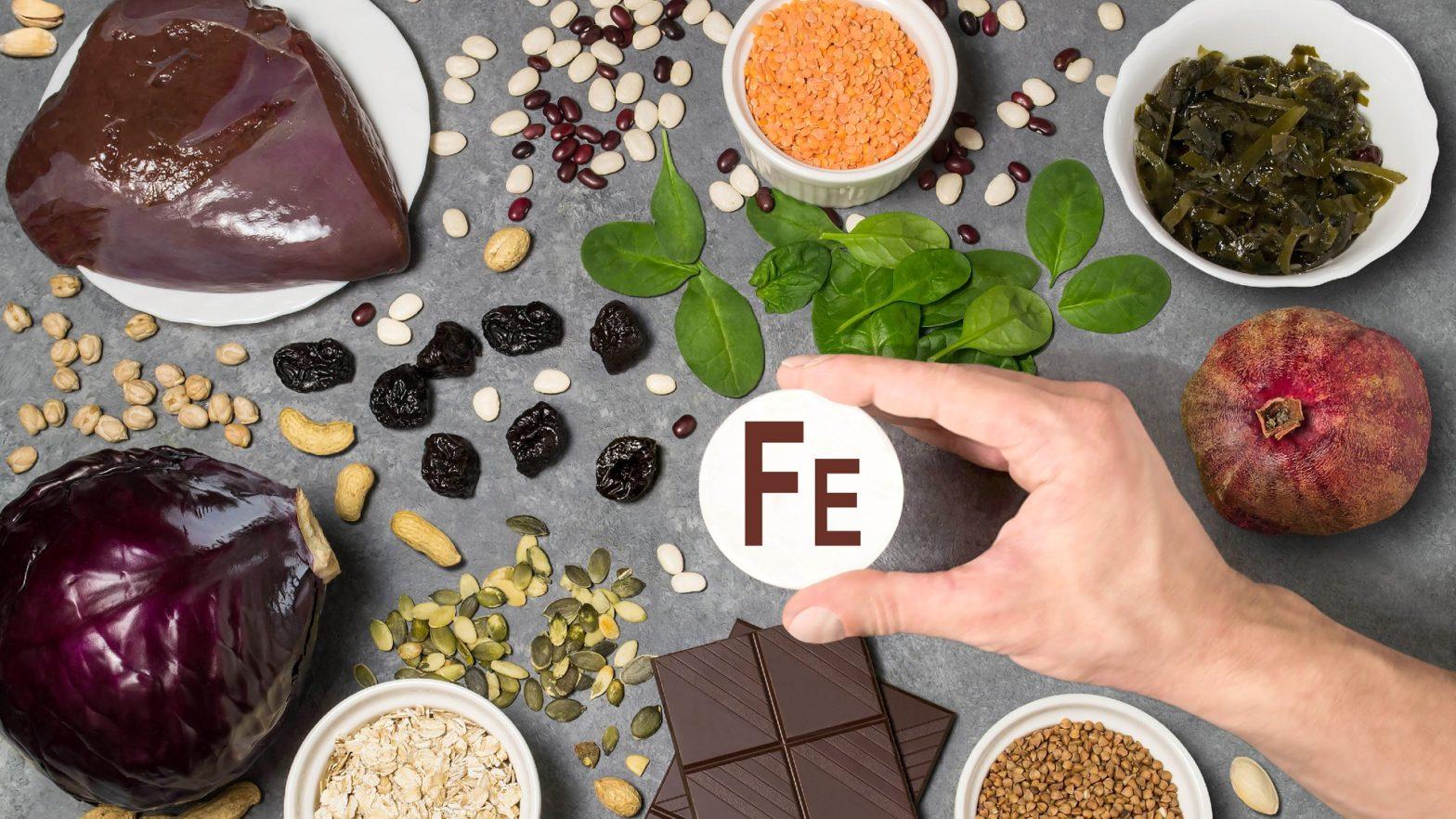 Diversos alimentos ricos em ferro (figado, semente de abóbora, folhas verdes) distribuidos em cima da mesa e uma mão segurando a sigla FE par simbolizar o elemento ferro.
