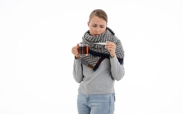 Mulher com roupa de frio com uma xícara de chá de artemísia e um termômetro.