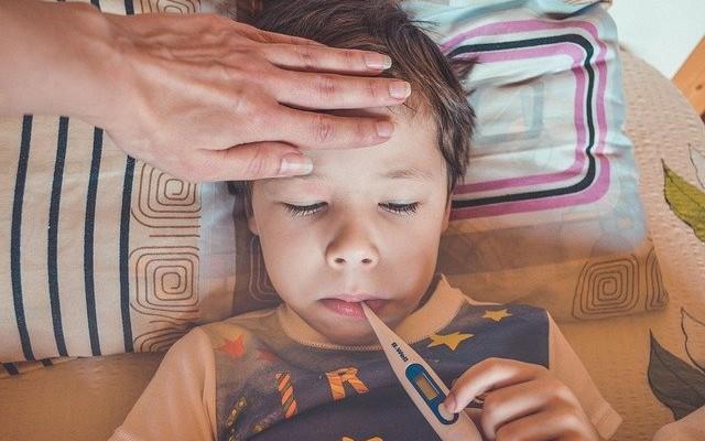 Criança deitada na cama segurando um termômetro digital que esta dentro de sua boca.